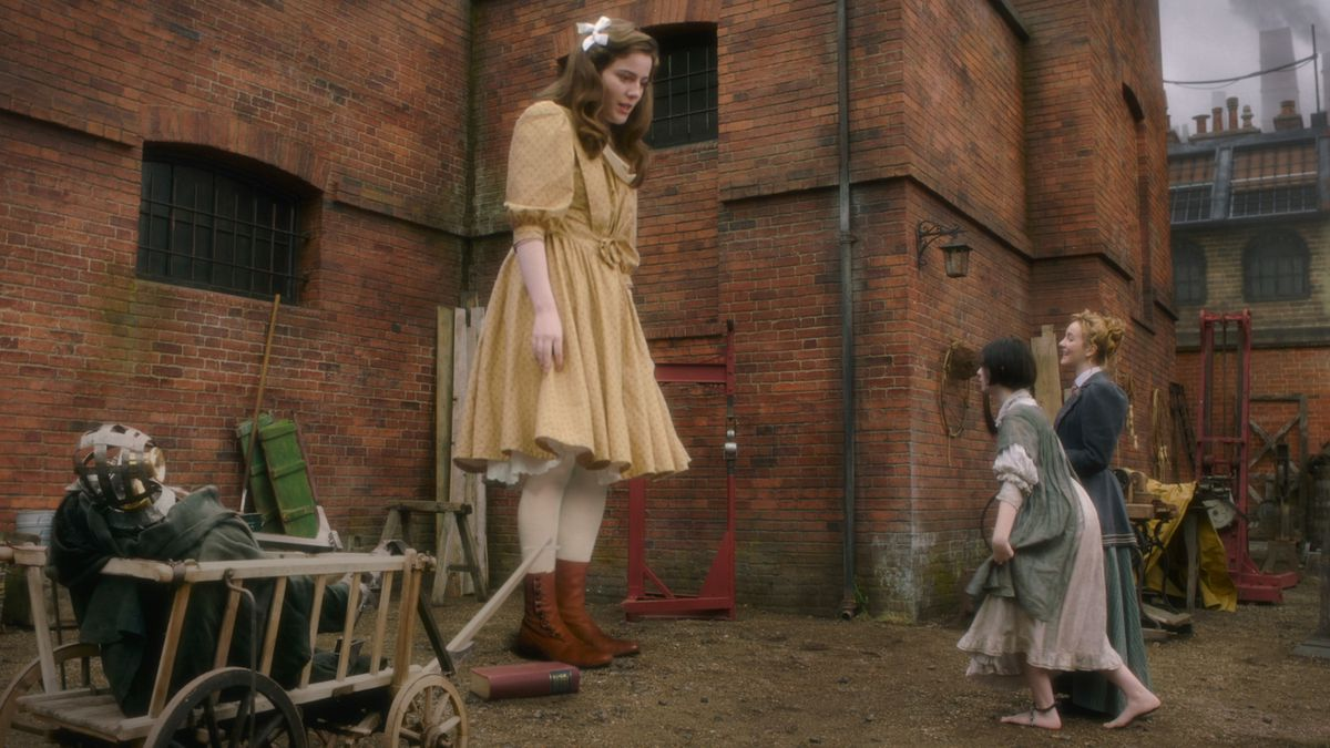 Primrose, a 10-foot tall girl, towers above her friends in The Nevers.