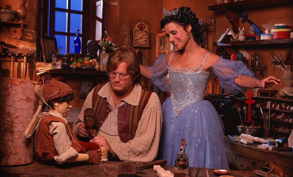 Julia Louis-Dreyfus as the Blue Fairy beams over Drew Carey as he carves his wooden son Pinocchio in Geppetto