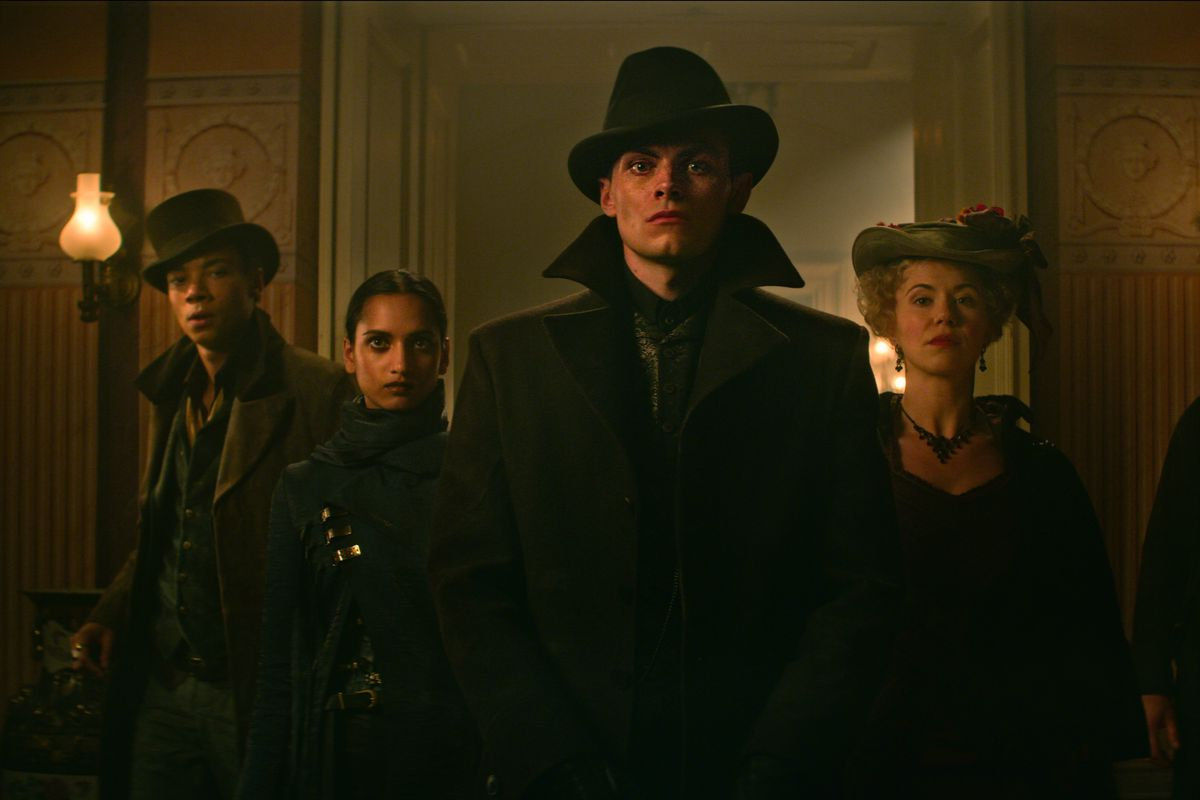 jesper, inej, and kaz, along with an older woman, in shadows
