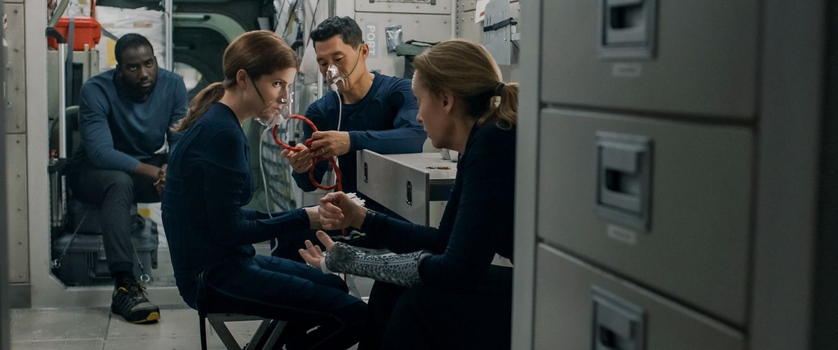The cast of Stowaway in their galley, with Anna Kendrick and Daniel Dae Kim wearing oxygen masks, Toni Collette sitting close to them, and Shamier Anderson sitting in the background