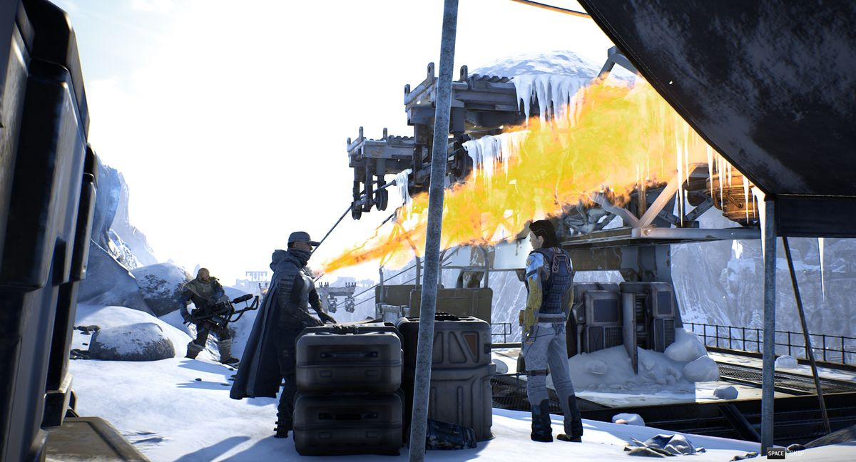 Three Outriders characters gather by some crates. One of them uses a flamethrower in the background