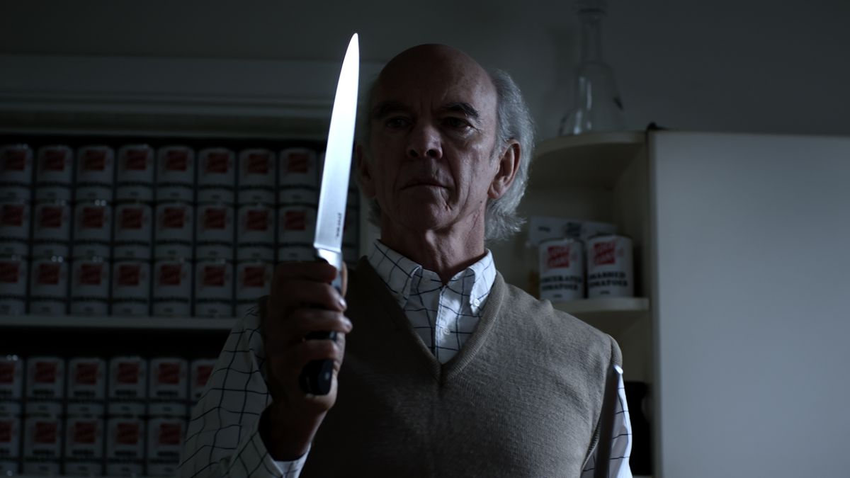 A man stands in a dark kitchen and holds up a large knife, backgrounded by hundreds of identical soup cans stacked neatly