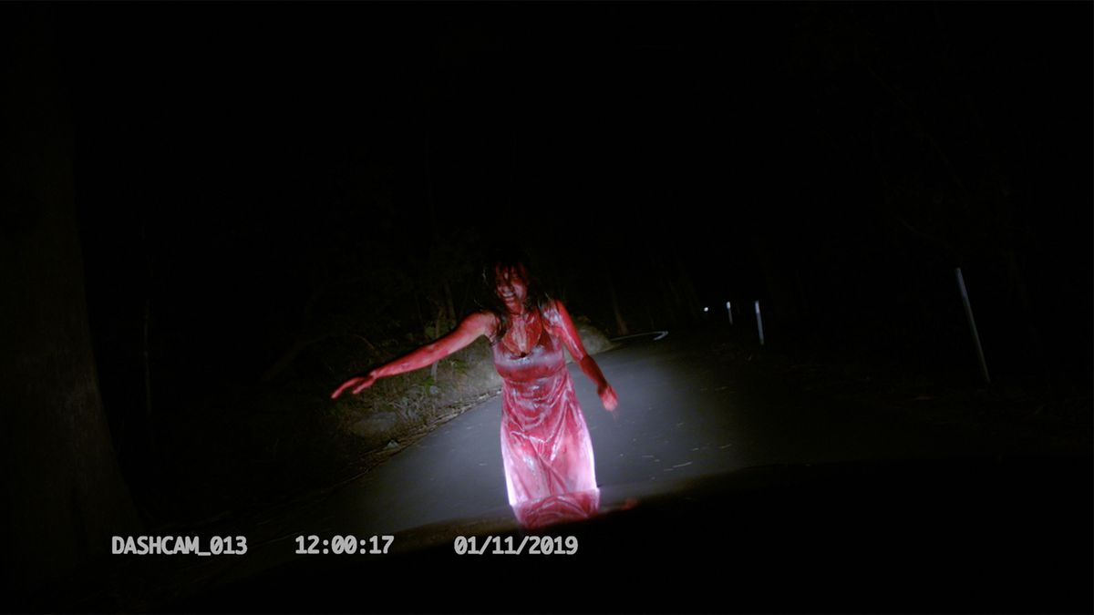 A blood-covered woman in a white dress, seen in dashcam footage in Deadhouse Dark