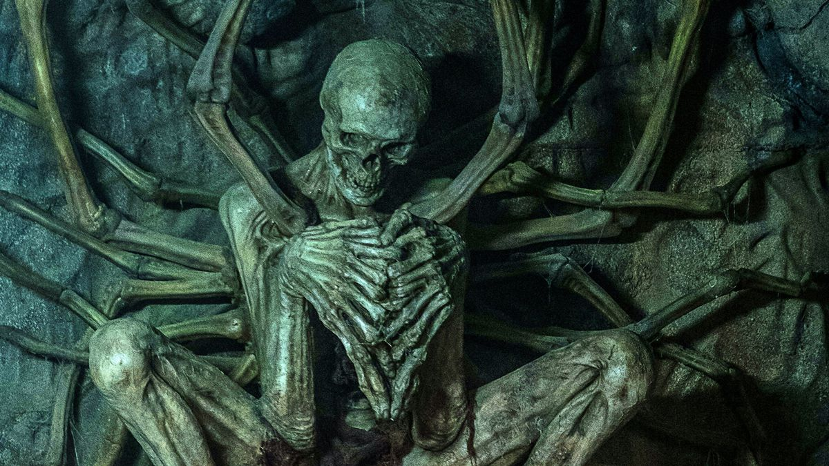 A gigantic malformed skeleton with steepled hands in David Prior's cosmic thriller The Empty Man