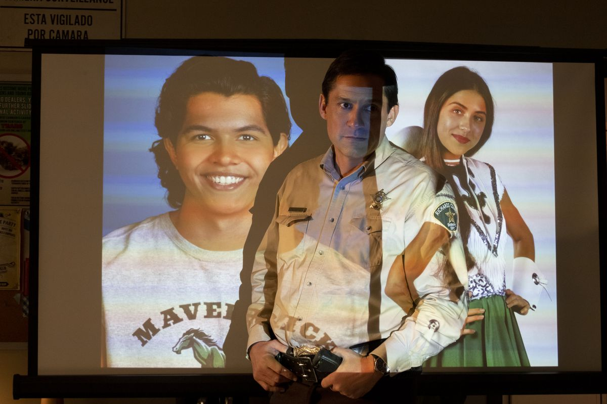 Panic's sheriff stands in front of a projection of the two teenagers who died in a previous game of Panic