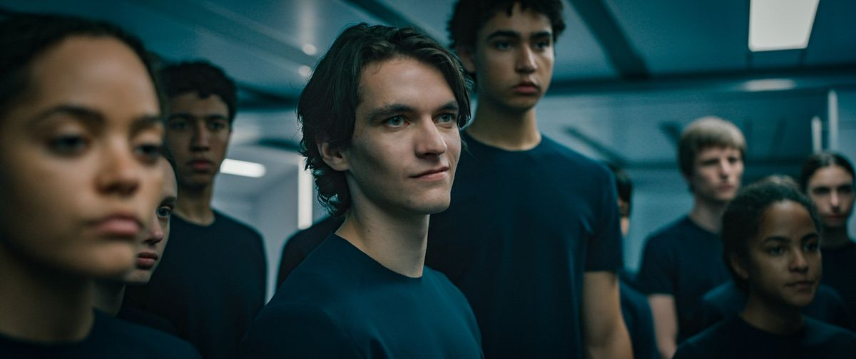Fionn Whitehead smirks rebelliously amid a crowd of blank-faced teenagers in Voyagers