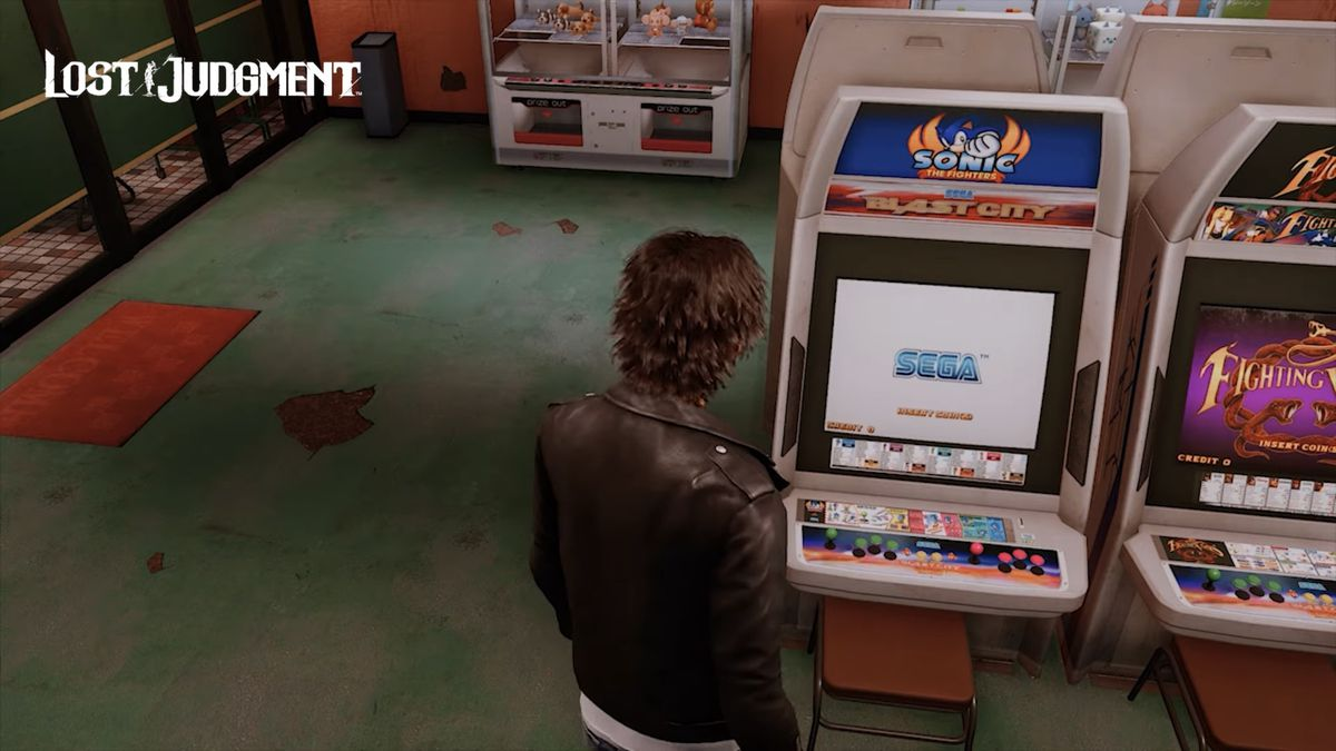 Takayuki Yagamilooks at a Sonic the Fighters Blast City arcade cabinet in an arcade in Lost Judgment