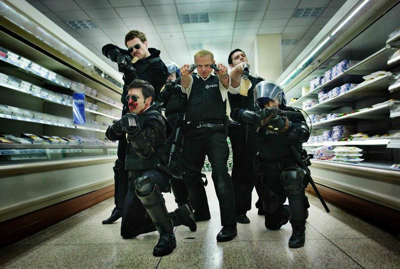 Simon Pegg as PC Nicholas Angel stands with his fellow officers in a well-lit shopping aisle, hold twin pistols akimbo style