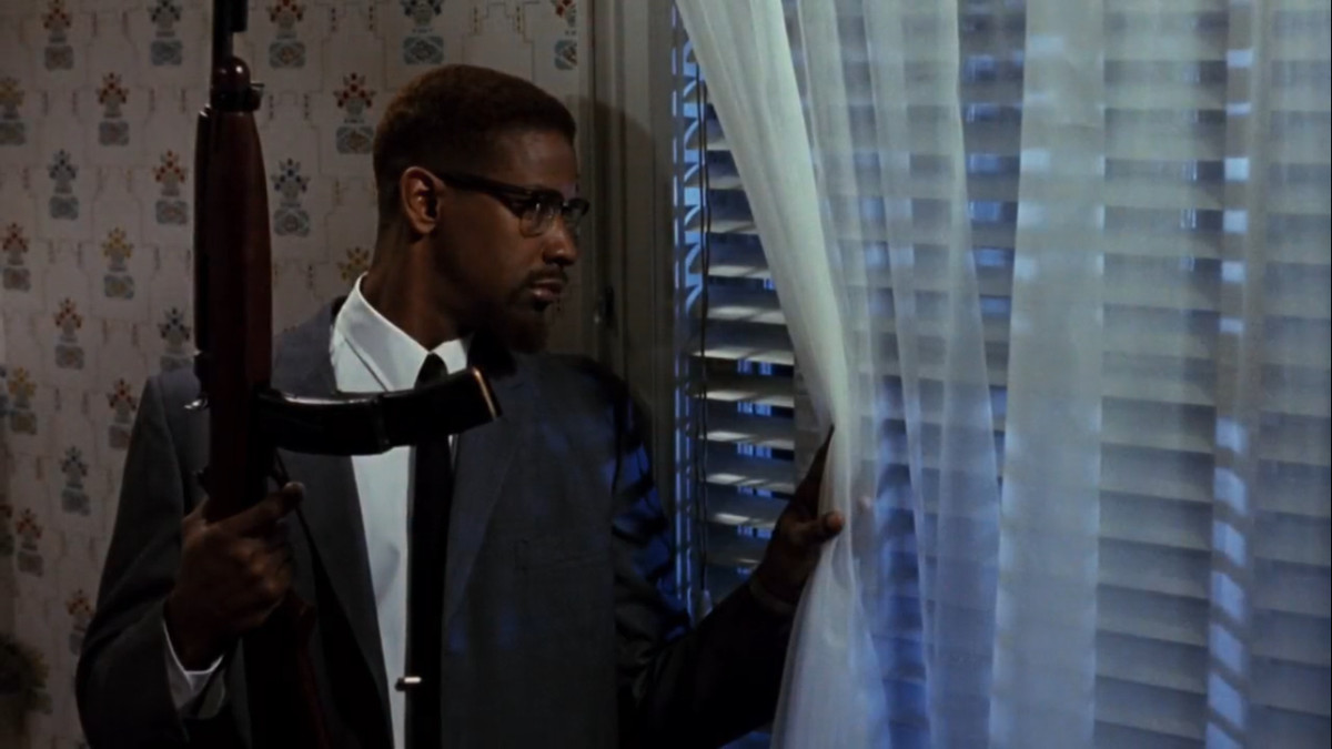 Denzel Washington peering out the window with a rifle as Malcolm X in Malcom X
