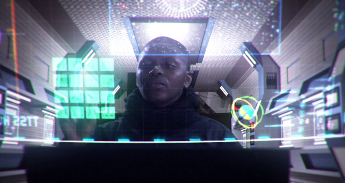 A Black man sits behind a control panel with multiple holographic light displays in The Tomb
