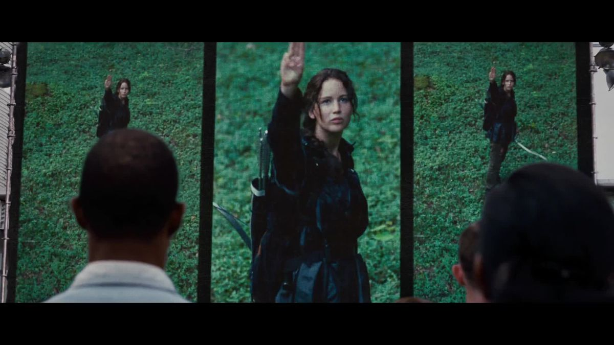 Several people seen from behind watch on a series of monitors as Katniss Everdeen gives the Mockingjay hand sign in The Hunger Games