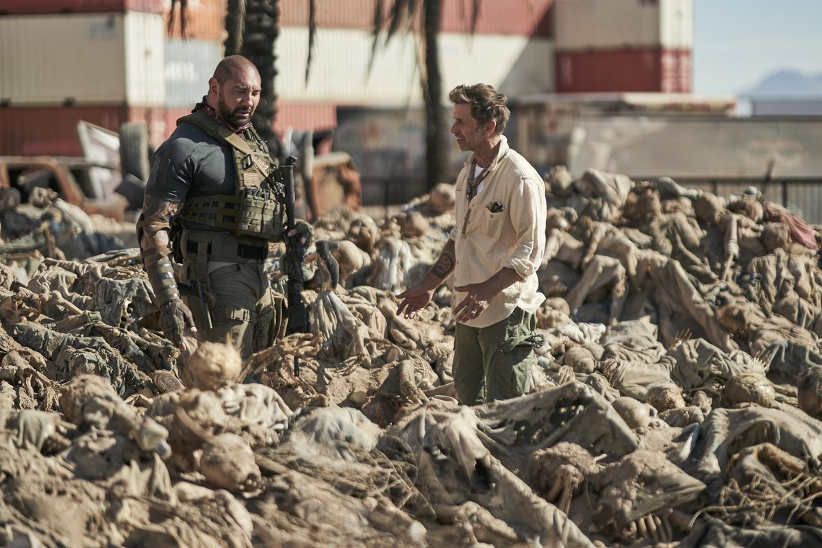 Dave Bautista and Zack Snyder stand in a field of corpses on the Army of the Dead set