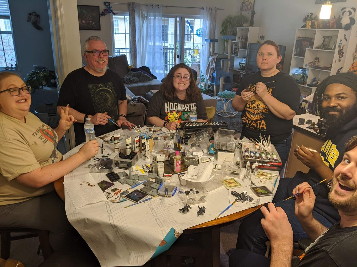 A group of players sits around a table covered with wrapping paper. Paints are spread out and miniatures are being worked on.