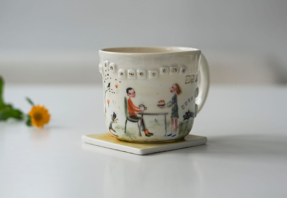 A ceramic mug with a pleasant scene on it. Scrabble tiles flow around the rim.