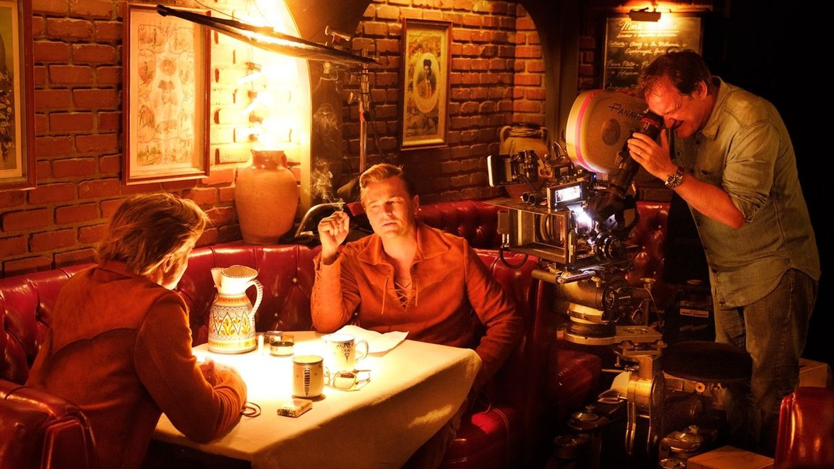 Brad Pitt and Leonardo DiCaprio sit facing each other in a restaurant booth as Quentin Tarantino watches from behind the camera filming Once Upon a Time ... in Hollywood