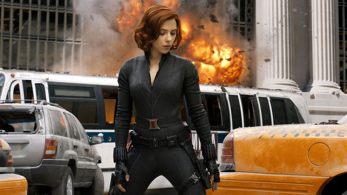 Black Widow standing in New York City with an explosion above a bus behind her