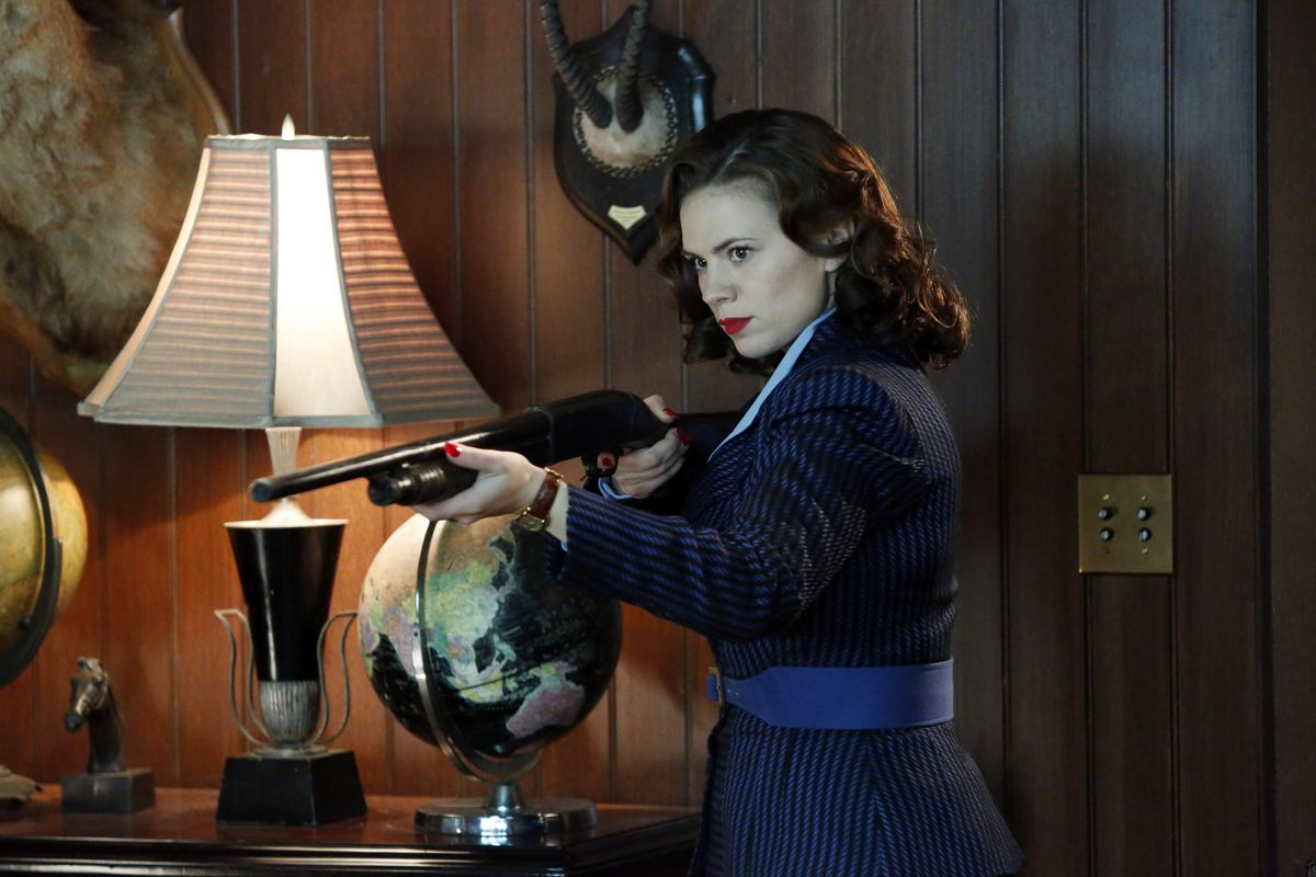Agent Carter holds up a shotgun in someone's wood den