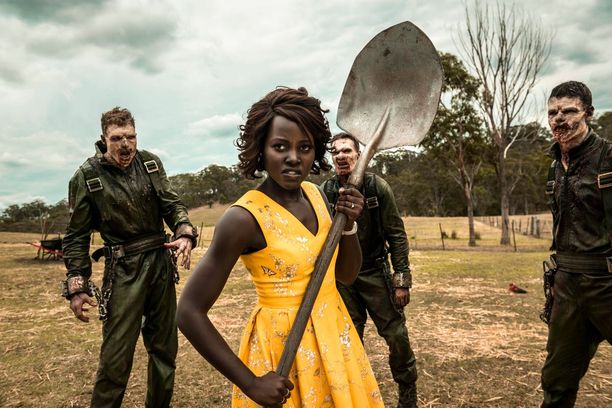Lupita Nyong'o brandishing a shovel while surrounded by zombies in Little Monsters