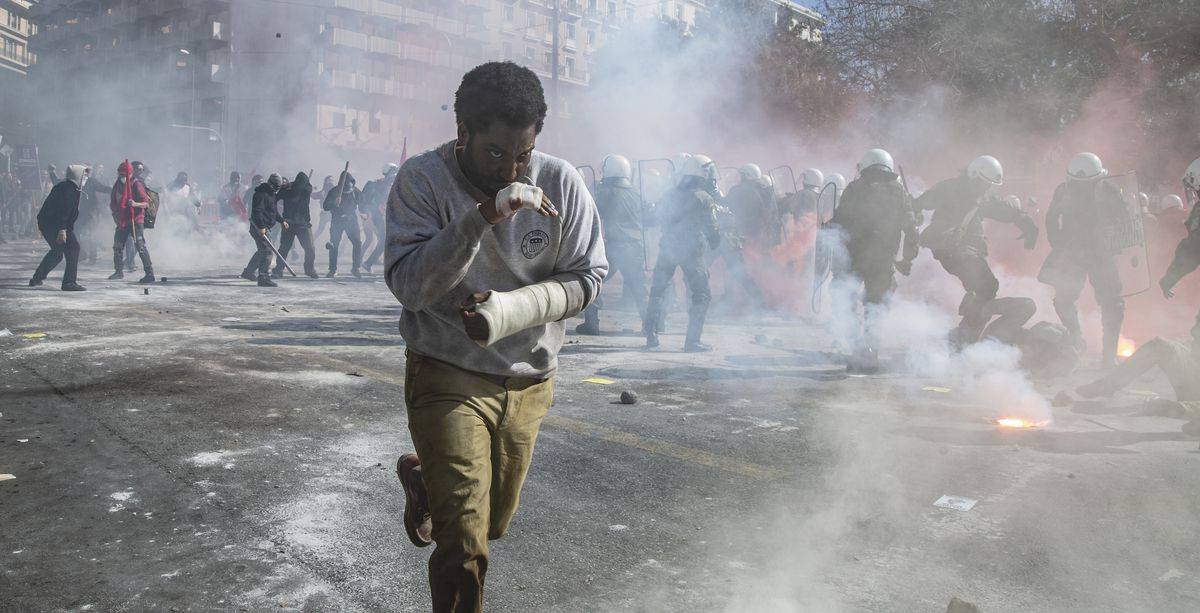 Beckett protagonist John David Washington, hands bandaged and bloodied, runs through the smoke-filled streets as a riot takes place in the background
