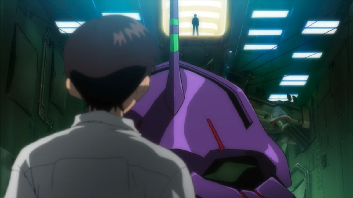 Shinji stands in front of his Evangelion with his father looming in the background in Evangelion: 1.0 You Are (Not) Alone