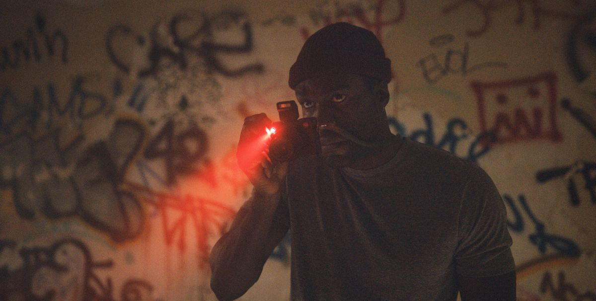 Yahya Abdul-Mateen II stands in a dark room, aiming a camera at graffiti in the 2021 Candyman