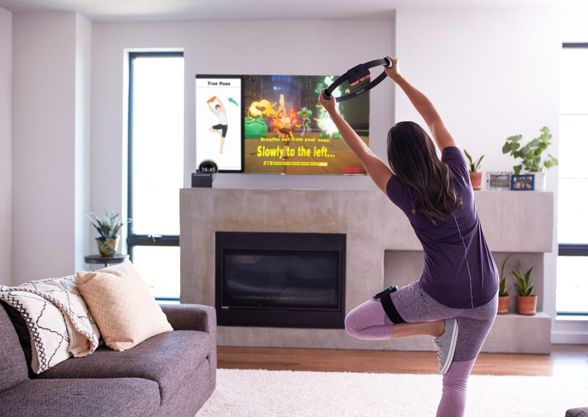 a woman in exercise gear holds a yoga pose with the Ring-Con while playing Nintendo's Ring Fit Adventure