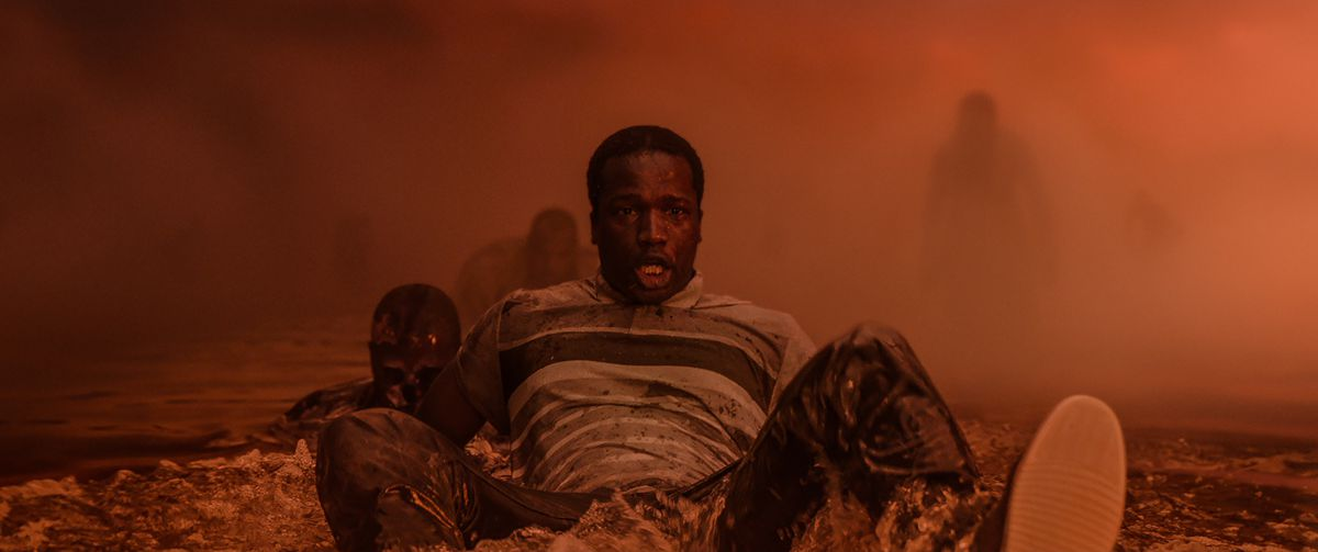 A terrified Black man sits in a foggy orange landscape, with looming shadowy figures in the background