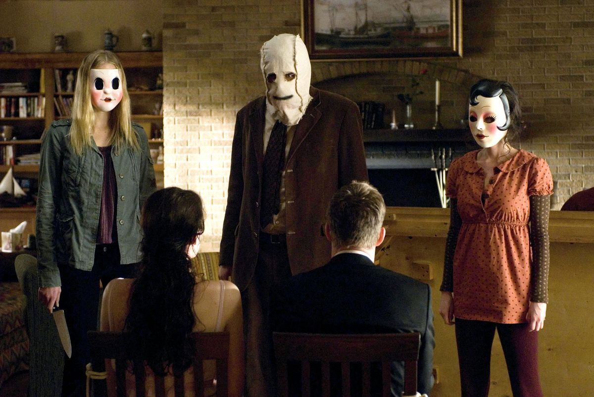 Three masked killers stand in front of a couple tied to chairs in their living room in The Strangers