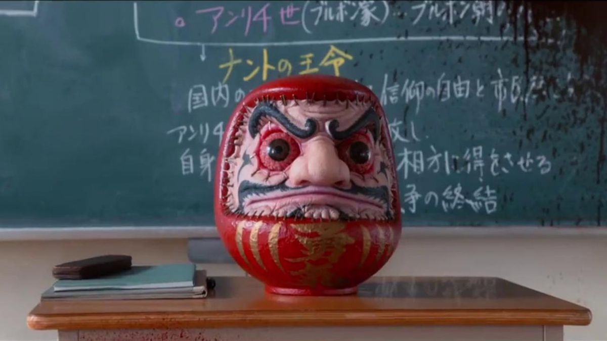 A mad-eyed statue sits on a desk in a classroom