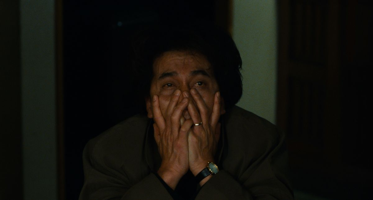 Detective Takabe (Kôji Yakusho) claspes his hands over his face in exhaustion and horror in Cure (1997)